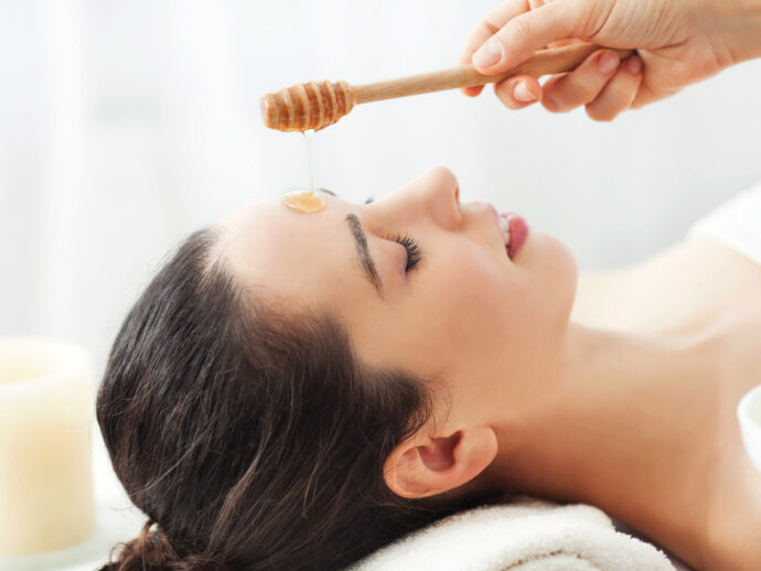 Woman waits patiently as a hand pours honey onto her face for a face mask